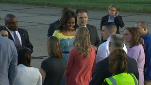 Mrs Obama was wearing a yellow and blue summer dress.