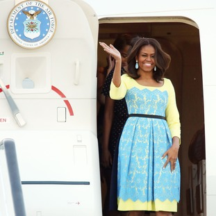 Michelle Obama waves as she steps off the plane at Stansted Airport