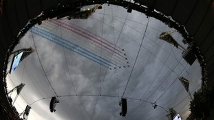 The Red Arrows leave coloured smoke trails as they fly over the Olympic Stadium