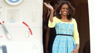 Michelle Obama waves as she arrives at Stansted Airport on Monday.