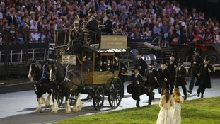 Performers run next to a horse-drawn wagon during the Opening Ceremony