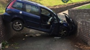 Woman and child survive crash which leaves car wedged in underpass