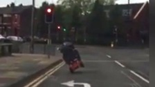 The scooter rider was captured on two wheels on a main road in Eccles