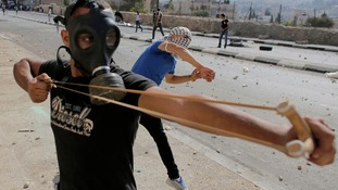 A Palestinian protester uses slingshot to hurl stones at Israeli troops following a demonstration.
