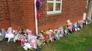 Balloons, flowers and cuddly toys line the bottom of the block of flats