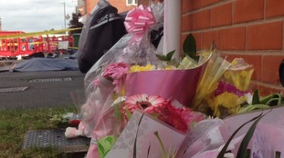 Well-wishers have left flowers and cuddly toys at the scene of the fatal fire