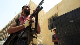 Free Syrian Army member aims his weapon after hearing shooting in Aleppo.