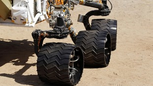 Three of six 20 inch aluminum wheels are seen on an engineering model of NASA's Curiosity Mars rover.