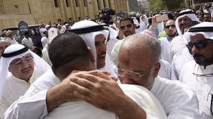 Kuwaiti Information Minister Sheikh Salman al-Humoud al-Sabah (C) consoles worshippers outside the Imam Sadiq Mosque