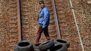 A striking worker walks past a pile of tires put on the Eurotunnel train tracks before being set on fire.
