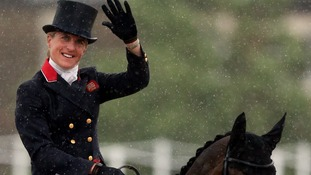 Great Britain's Tina Cook waves whilst riding Miners Frolic in heavy rain during the Dressage stage of the Eventing at Greenwich Park.