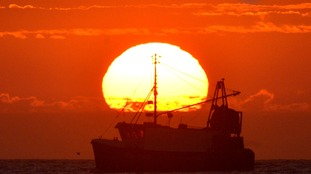 A fishing boat in front of the rising sun.