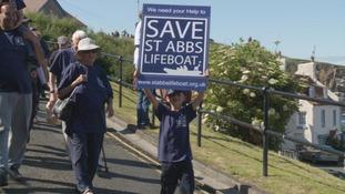 little boy holds a sign