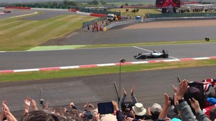 Crowds cheering as Lewis Hamilton wins the British Grand Prix for the third time.