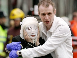 Paul Dadge helps someone injured in the Edgware Road bomb.
