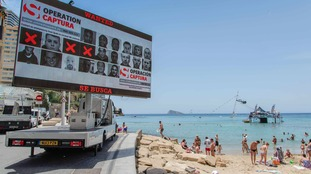 A 13ft digital screen broadcasting photos of fugitives.