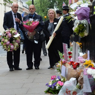 George Psaradakis (second left), the driver of the number 30 bus that was blown up in Tavistock Square, leaves flowers close to the scene of the bombing