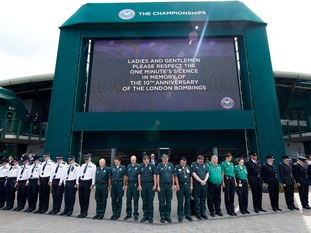 Members of staff working within the Wimbledon grounds observe a minute's silence to commemorate the 10th anniversary of the 7/7 attacks