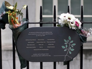 A memorial plaque is attached to railings in Tavistock Square