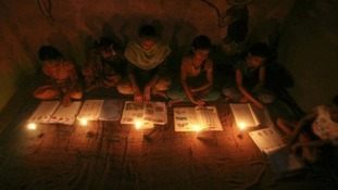 Muslim girls study in the light of candles inside a madrasa or religious school during power-cut in Noida on the outskirts of New Delhi.