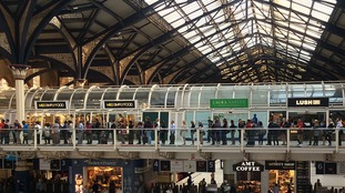 People queue for buses inside Liverpool Street Station