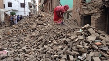 A woman sifts through rubble in Siddhipur where 11 people died