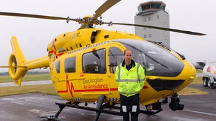 The Duke of Cambridge stands by a helicopter as he begins his new job with the East Anglian Air Ambulance (EAAA) at Cambridge Airport.