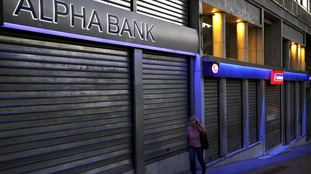 A woman walks by bank branches protected by security shutters in Athens.