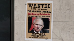 A poster depicting a defaced image of German Finance Minister Wolfgang Schaeuble on the wall of a Eurobank branch in Athens.