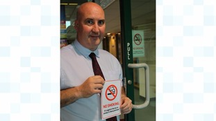 SLDC Environmental Health Officer Peter Adams with a no-smoking sign that businesses are legally required to display at all entrances to their premises