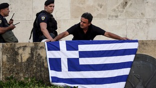 An anti-EU protester unfurls a Greek national flag next to riot police on the steps in front of the parliament.