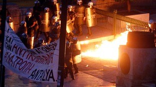 Greek riot police battle flames in Athens.