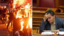 Riots take place outside parliament as inside the Greek finance minister holds his head in his hands.