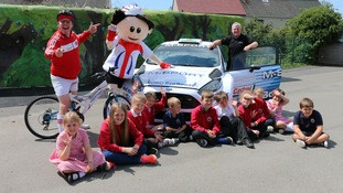 Standing from left to right next to the M-Sport rally car behind the seated children from All Saints Primary, Cockermouth are Mr Stretch (Active Cumbria performer), ToBi (Tour of Britain mascot) and John Hilton, Project Director from United Utilities