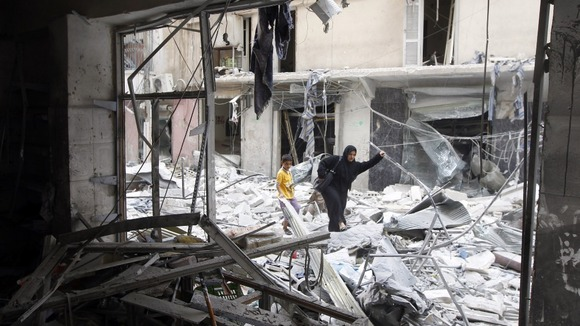 A woman walks through rubble from a building destroyed by shelling from forces loyal to Syrian President Bashar Al-Assad in downtown Aleppo