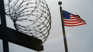 US flag flies above a razorwire-topped fence at the Camp Six detention facility