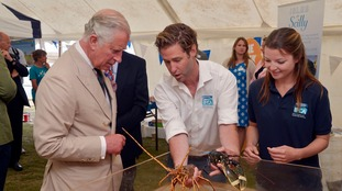 The Prince of Wales is shown crustaceans as he visits the Island Fair.