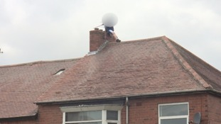 A boy climbs onto the roof of a house in Newcastle