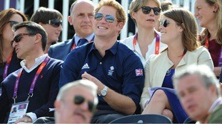 Prince Harry shares a joke with Princess Eugenie as they watch the Olympic Eventing