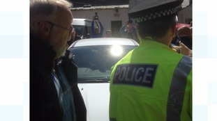 Police escorted David Mundell's car through the crowd.