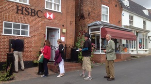 Bank customers at HSBC in Reepham queue for the bank machine.
