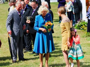 A young girl hides behind her mother after she handed a bouquet of flowers to the Duchess of Cornwall