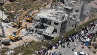 Israeli paramilitary police and Jewish settlers stand near two partially-built dwellings during their demolition in the West Bank