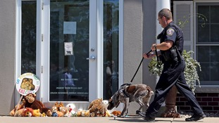 A sniffer dog examines the scene outside Palmer's office in Bloomington