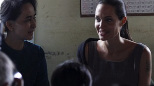Burma's opposition leader Aung San Suu Kyi and Jolie meet with female factory workers at their hostel.