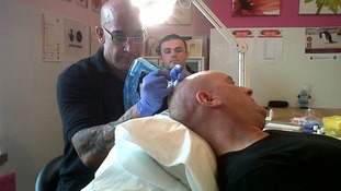 Mr Dalgleish having the procedure done again by a trained tattooist
