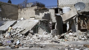 A Syrian child inspects his damaged house after further shelling in the Kadam district area near Damascus.