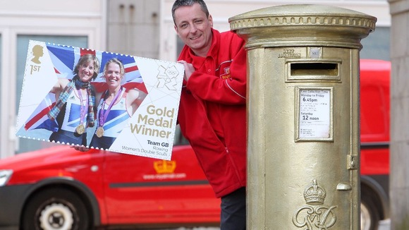 Postman Steve Allan at a golden post box to celebrate rower Katherine Grainger&#x27;s gold medal in Aberdeen.