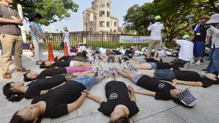 Children perform a die-in in front of the Atomic Bomb Dome at Peace Memorial Park in Hiroshima