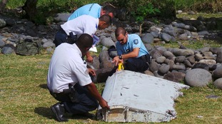 French gendarmes and police inspect a large piece of plane debris found on Reunion.